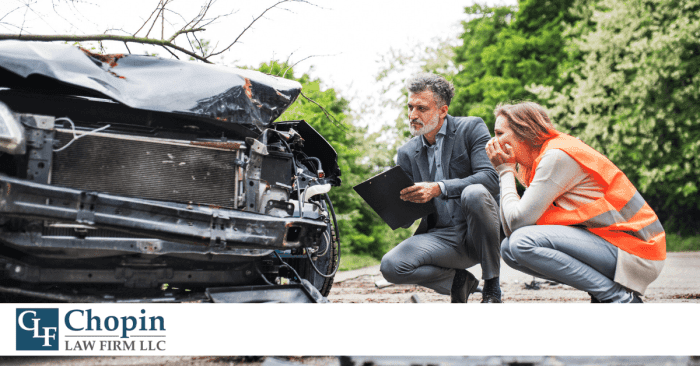 Image of a man and woman looking at a car, noting down damage from an accident